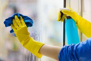 Mitarbeiterin von bavaria Cleaning führt Glasreinigung am Fenster in München durch