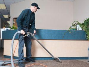 Mitarbeiter von Bavaria Cleaning staugt im Zuge der Unterhaltsreinigung den Empfangsbereich einer Firma