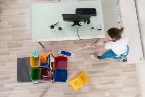 Von oben Blick auf Mitarbeiterin von Bavaria Cleaning, die eine Büroreinigung durchführt