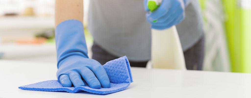Reinigung von Tischoberfläche mit einem blauem Tuch