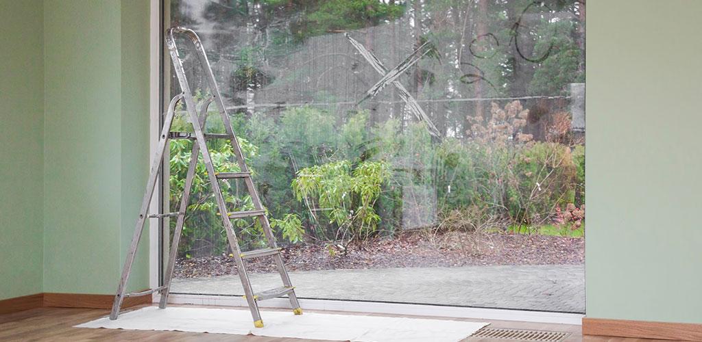 Leiter steht vor dreckiger Scheibe für eine Glasreinigung